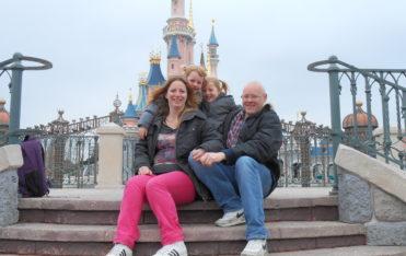 Karin met haar man en kinderen geposeerd voor de ingang van Disneyland